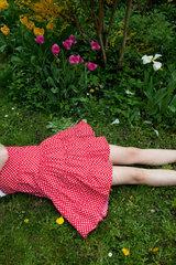 Freiburg  Deutschland  ein Maedchen im Kleid liegt im Garten  Ausschnitt