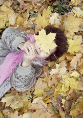 Little girl lying on bed of autumn leaves