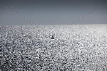 Solitary sailboat at sea