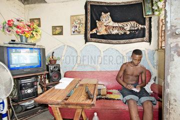 Santiago de Cuba  Kuba  Jugendlicher verpackt in der Wohnung Erdnussriegel fuer den privaten Strassenverkauf