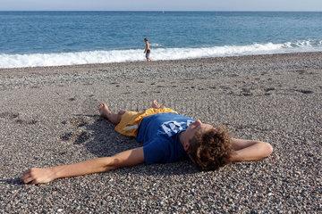 Taormia  Italien  Junge liegt entspannt am Strand