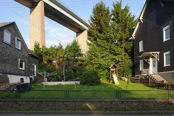Siegen  Deutschland  Wohnstrasse mit Einfamlienhaeusern und die Siegtalbruecke