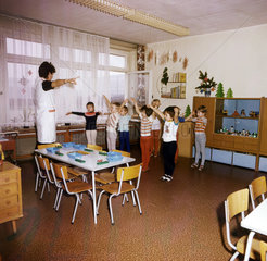 Weimar  DDR  Kindergartenkinder und Erzieherin machen vor dem Mittagessen Gymnastik