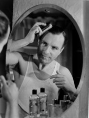 Man brushing his hair in a mirror  c 1950s.