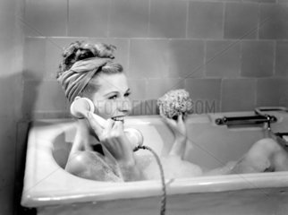 Woman lying in a foam bath answering a telephone call  c 1950s.