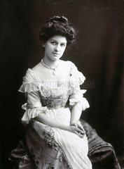 Young woman sitting in an elaborate dress  1890s.