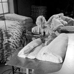A seamstress sews an asbestos mattress  Thomas Ward Asbestos  1961