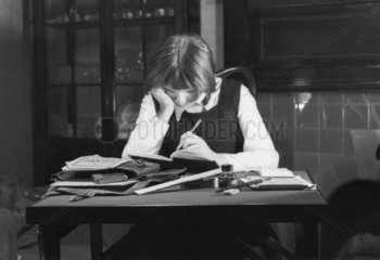 Schoolgirl doing her homework  c 1930s.