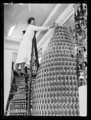 Shop assistant building giant tower of Heinz beans  c 1960s.