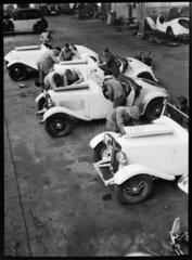 Mechanics work on the engines of three motor racing cars  Germany  c 1934.
