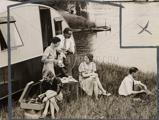 Caravanners having tea by a lake  June 1934.