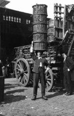 Market porter balancing baskets on his head  London  c 1910s.
