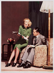 Woman reading a magazine on the arm of a man's chair  c 1940s.