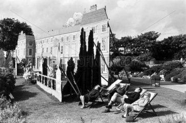 People in deckchairs by an outdoor set  1960s.