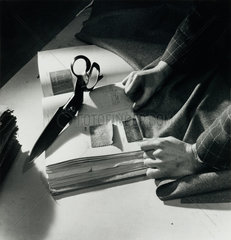 Study of storeman's hands as he matches cloth patterns in ledger  1948.