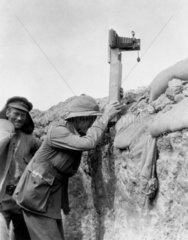 Soldier taking a photograph with a camera attached to a periscope  c 1915.