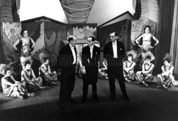 Three Music Hall performers flanked by chorus girls.