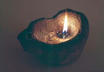 Primitive lamp  a stone used as a floating wick holder  1801-1900.
