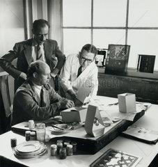 Management and designer discuss easter egg packaging  1956.