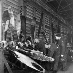 Men repairing damaged aircraft propellers