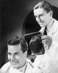 Man inspecting the back of his new haircut in a barber's mirror  c 1940s.
