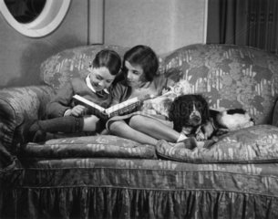 Two children on a settee reading 'Uncle Oojah's Big Annual'  c 1930s.