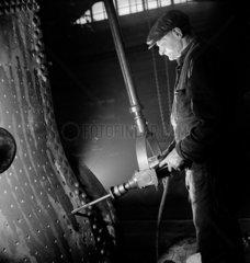 A fitter drills a steam engine firebox  Swindon  1948.