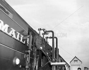 Steam locomotive collecting mail  1930s.