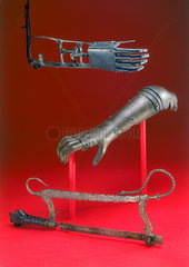 Amputation saw and two artificial arms  16th century.