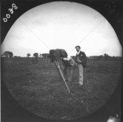 Two men in a field taking a photograph witha plate camera on a tripod  c 1890s.
