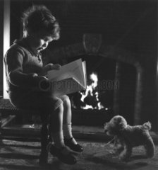 Small boy reading a book by a fireside  c 1930s.