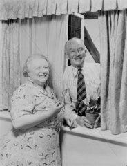 Elderly couple by a window  c 1950.