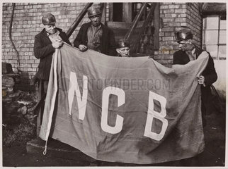 Four miners with the NCB flag  1946.