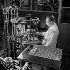 An engineer seals valves at Mullard Ltd  1955.