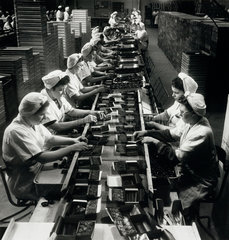 """A team of female workers on long line packing boxes of """"Fortune � chocolates."""