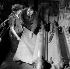 A male inspector with female worker ring weaving sheets of asbestos material.