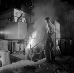 Two foundry men pour molten steel in a HF furnace for tool making  1966.