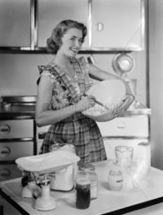 Woman holding a mixing bowl  1952.
