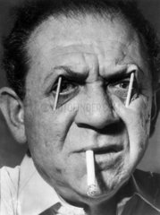 Sid James with matchsticks in his eyes  whilst smoking a cigarette  1959.