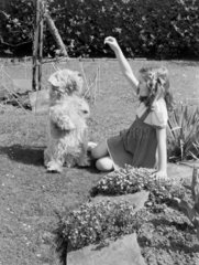 Girl playing with a dog in a garden  1949.