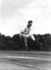 Long jumper in action  c 1920s.