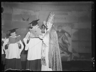 A child bishop and choir sing Christmas carols  1936.
