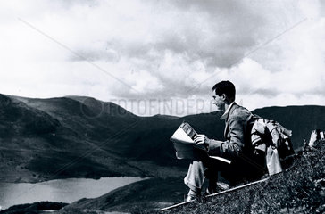 Rambler map-reading on a hill top  c 1930s.