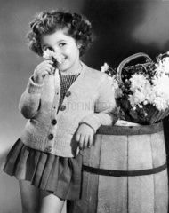 Child smelling a flower  1940s.