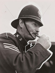 A policeman blowing a whistle  1938.
