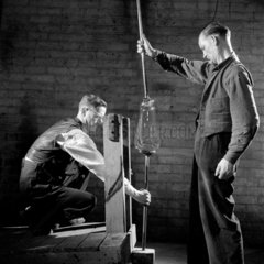 Two glassworkers put blown glass bulb onto platform  Lemington   1960.