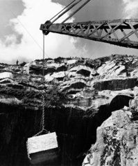 Workers look from brow as crane lifts Bodmin granite block from quarry  1961.