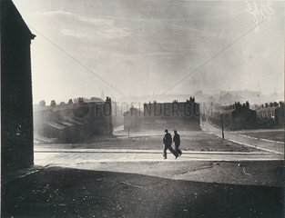 Silhouetted figures walk by a cleared blitz site  Liverpool  21 November 1949.