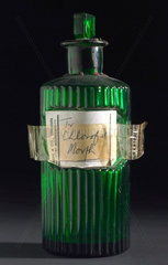 Green glass bottle containing chloroform and morphine  1900-1979.