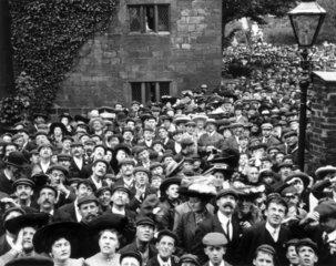 Crowd of people all looking skyward  c 1900